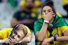 Brazil supporters holding Neymar face masks react after Germany defeated Brazil 7-1 to advance to the finals during the World Cup semifinal soccer match between Brazil and Germany. Photo / AP