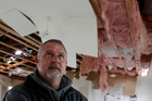 Dave Collett checks the damage to a rented house on his Hikurangi farm which had its roof blown off in the big storm. Photo / Tania Newman