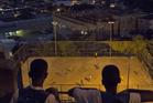 Two boys watch kids play pelada at the Mangueira slum in Rio de Janeiro, Brazil. Photo / AP