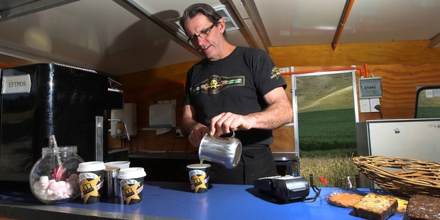WARM INSIDE: Dave Robertson in the mobile Espresso Man coffee cart, where he will hove-to in Central Hawke's Bay while the bad weather passes so that he cane resume his run-walk-bike journey from North Cape to Bluff.