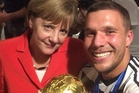 Chancellor Angela Merkel with a member of Germany's World Cup-winning football team, Lukas Podolski, in Rio de Janeiro.
