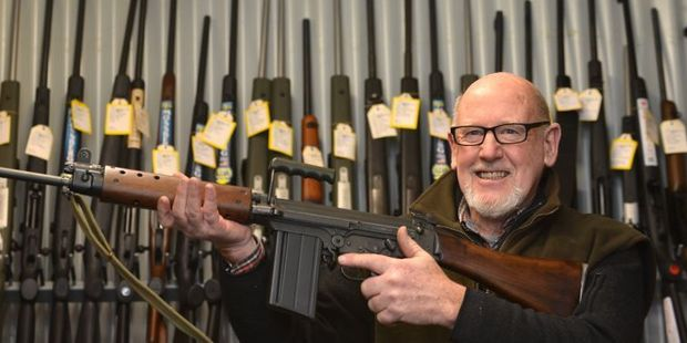 Centrefire McCarthy managing director Selwyn Shanks, holding a FN FAL L1A1 military-style semi-automatic, says cheaper weapons have helped boost firearms sales. Photo / Peter McIntosh