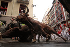 Revelers run as Miura fighting bulls fall during the running of the bulls at the San Fermin festival, in Pamplona, Spain. Two Australians and a Spaniard were gored. Photo / AP