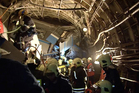 Frame grab from a video showing rescue teams working inside the tunnel where several cars of the wrecked train look almost coiled. Photo / AP