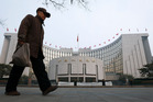 An elderly Chinese man walks past the headquarters of the People's Bank of China in Beijing. Photo / AP