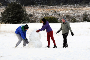 Tourists make the most of the snow on the lawn of the Chateau Tongariro, National Park. Photo / Ross Setford