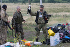 A pro-Russian fighter holds up a toy found among the debris at the crash site of a Malaysia Airlines MH17 near the village of Hrabove, eastern Ukraine. Photo / AP