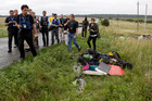 Representatives from the OSCE (Organization for Security and Co-operation in Europe) delegation inspect passengers' personal luggage collected at the site of MH17. Photo / AP