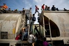 Central American migrants climb on a train heading towards the United States border with Mexico. Photo / AP