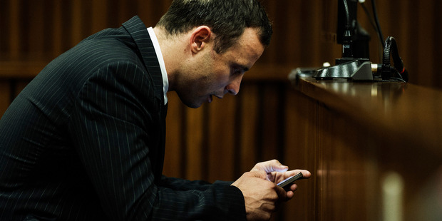 Oscar Pistorius, seen here checking his phone in court, has posted a series of strange tweets.  Photo / AP