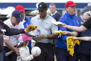 Tiger Woods signs autographs for fans as he leaves the practice green ahead of the British Open. Photo / AP