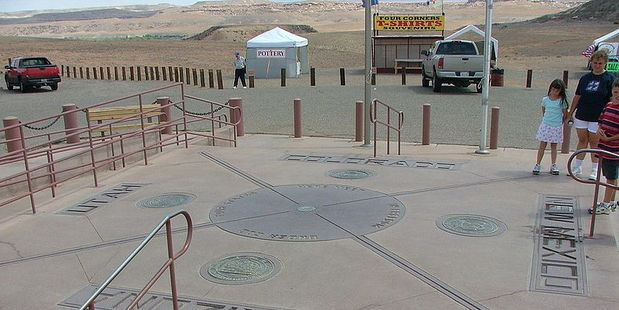 Tourists stand on the New Mexico side of the Four Corners Monument, which supposedly marks the point where Utah, Arizona, Colorado and New Mexico meet.