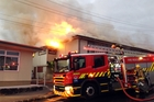 Fire crews battle the blaze at the school. The fire ignited in a toilet block. Photo / SNPA