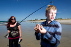 Te Puke 17-year-old Reuben Martin, right, baits his hook with the help of his sister, Rebecca Martin, on Papamoa Beach today. Photo / Alan Gibson