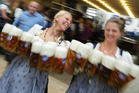 Waitresses carry beer mugs during the opening ceremony in the
