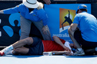 Frank Dancevic of Canada lies on the court after collapsing during his first round match against Benoit Paire of France as temperatures topped at 43 C (108 F). Photo / AP