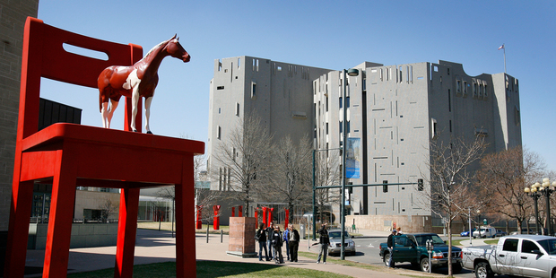 A sculpture of a horse standing on a chair stand in front of the North Building of the Denver Art Museum. The outer wall of the grey building is covered with glass tiles. Photo / Sarah Ivey