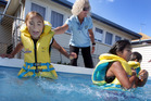 Cecilie Elliott, Swimming NZ safety adviser, helps Taylah Baker into the water as classmate Vanessa Corlett wades on.