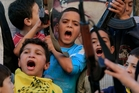 Palestinian children in Lebanon hold weapons and chant slogans against Israel after hearing of the death of Ariel Sharon.