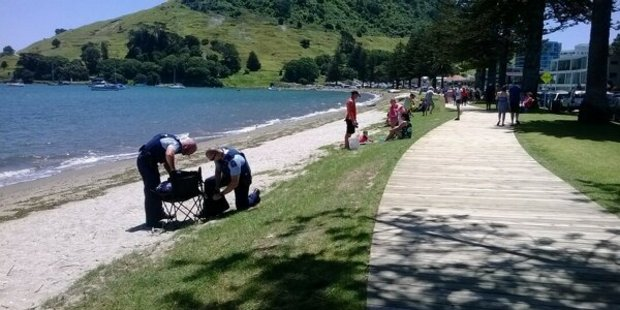 Police pack up the belongings of a man who is believed to have suffered a heart attack while snorkeling at Pilot Bay.