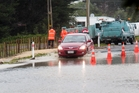 A car drives through surface flooding on Waimarama Rd yesterday afternoon. One lane of the road remained open. Photo / Warren Buckland