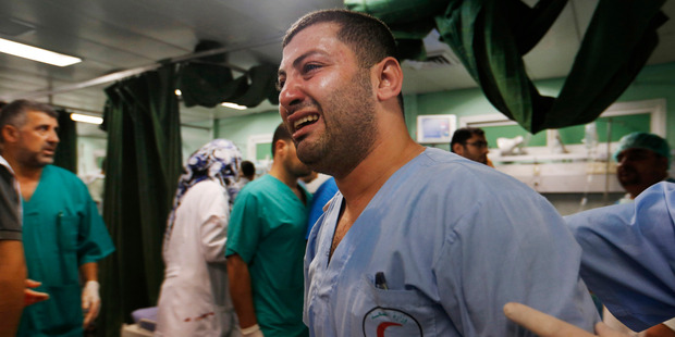 While the Hamas fighters show resilience, a Palestinian medic is overwhelmed by emotion as he takes a break treating wounded people by Israeli strikes. Photo / AP