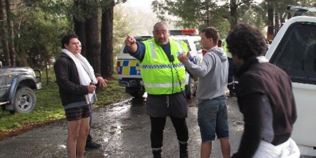 Sergeatn Riki Whiu speaks with Shan Owen during rescue operations near Haruru Falls.