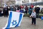 Judah Leung-Wai, aged 2, waves an Israeli flag during a pro-Israel peace rally in Midland Park, Wellington.