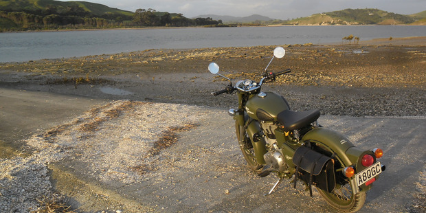 The Royal Enfield beside the Otamatea River opposite  where the  church that also served as a gunpowder magazine once stood.