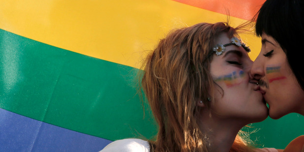 Two women kiss in front of a rainbow flag, the symbol of the gay rights movement, during the Gay Pride parade. Photo / AP
