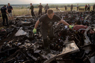 A man looks for the remains of victims in the debris at the crash site of Malaysia Airlines Flight 17 near the village of Hrabove, eastern Ukraine. Photo / AP
