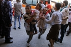 Palestinian medics carry children wounded in a strike on a United Nations school in Beit Hanoun. Photo / AP