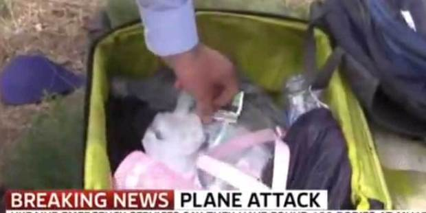 Sky News presenter Colin Brazier reaches into the luggage of a MH17 victim at the crash scene, in a You Tube screen grab.