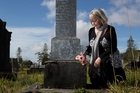 Sue Atkins at the grave of her great-uncle Robert Arthur Hislop (below), the first New Zealand soldier to give his life in the Great War. Photo / Richard Robinson