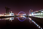 Glasgow's 'Squinty Bridge' and buildings alongside the River Clyde are illuminated at night. Photo / Thinkstock