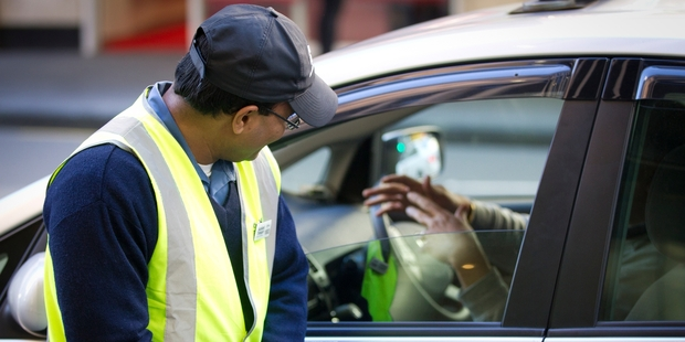 A parking warden, known only as Alak, tries to move on an unlawfully parked vehicle. Picture / Sarah Iveyv