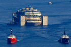The wreck of the Costa Concordia cruise ship is towed by two tugboats along the Tyrrhenian sea. Photo / AP