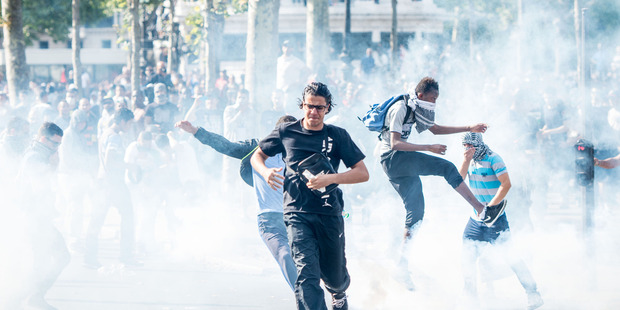 Pro-Palestinian protesters try to escape from a tear gas cloud thrown by riot police during a banned demonstration in support of Gaza at Place de la Republique in Paris, France. Photo / AP