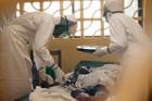 Dr Kent Brantly, left, treats an Ebola patient at the Samaritan's Purse Ebola Case Management Center. Photo / AP