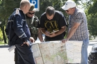 Ukrainian Ministry Emergency officer, left, Donetsk People's Republic fighter, 2nd left, and members of the OSCE mission in Ukraine examine a map of the MH7 crash area. Photo / AP