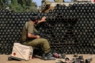 An Israeli reservist constructs a wall with the Star of David from cardboard shell boxes. Photo / AP