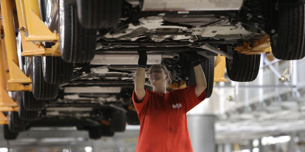 An assembly line worker builds cars in a US auto plant. The US economy grew at a faster than expected 4 per cent annual rate in the latest quarter after a grim start to 2014. Photo / AP