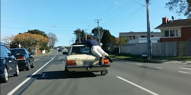 """Video footage of what appears to be a man """"surfing"""" off the back of a moving car is being slammed by road safety authorities. Photo / Supplied"""