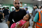 A Palestinian man carries a wounded girl into a hospital emergency room in Gaza. Photo / AP