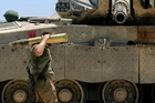 An Israeli soldier carries a tank shell near Gaza during shelling last week. Photo / AP