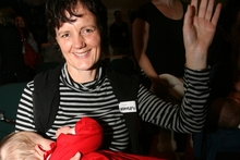LATCHED: Hayley Inder, of Masterton, with 9-month-old Mali, raises her hand to be counted.