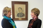 FAREWELL: In front of a photo of Selina Sutherland, who helped establish the first hospital in Masterton, is Cate Tyrer, left, taking over from Lesley O'Hara, who is retiring. PHOTO/SUPPLIED BY WAIRARAPA DHB