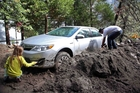 Andrew Watson and Taylor Becker dig out their car after rocks and mud inundated their Forest Falls home. Photo / AP
