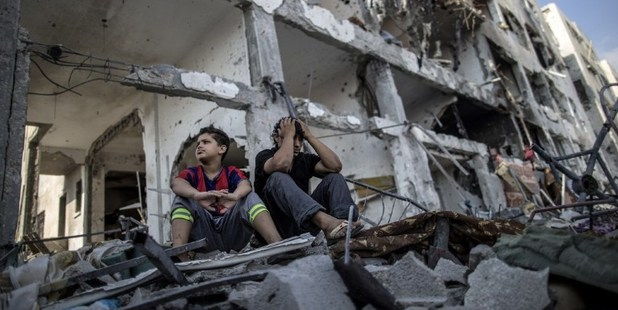 Palestinian brothers sit on the rubble of their house in front of an apartment block in part of the northern Beit Hanun district of the Gaza Strip. Photo / AFP