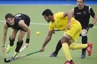 New Zealand's Simon Child, left, fights for the ball during the men's hockey semifinal between New Zealand and India. Photo / Greg Bowker